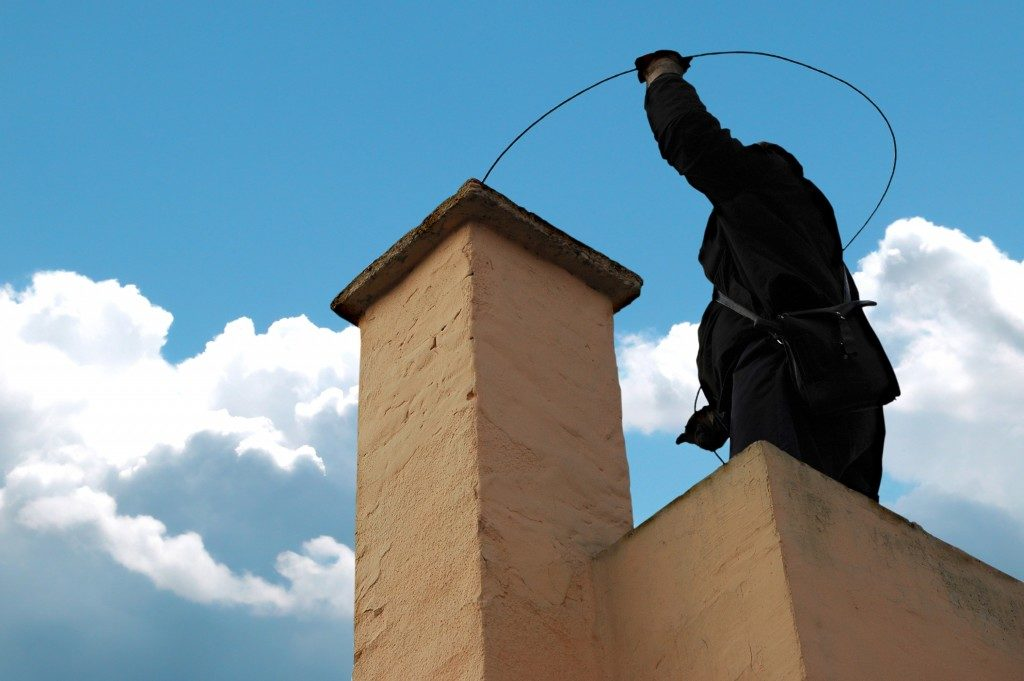 Chimney sweeper on the roof of a house