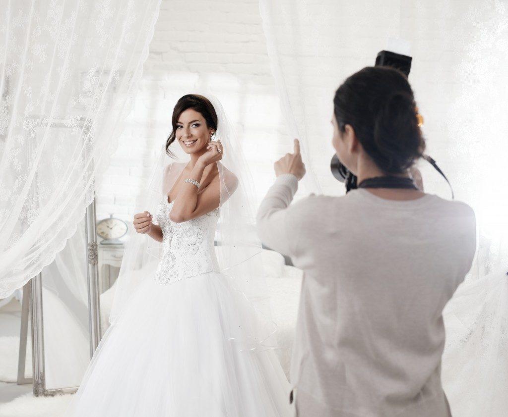 Female photographer photographing beautiful happy bride indoors.