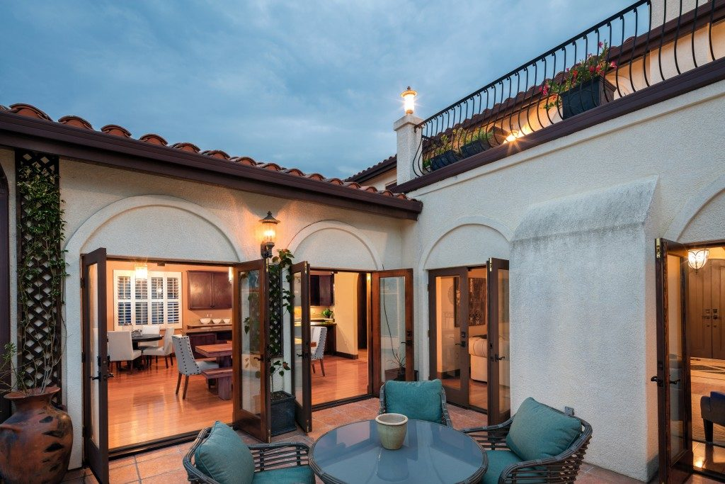 Amazing Mediterranean home at twilight with patio and open french doors
