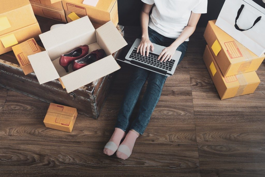 woman shopping online surrounded by packages