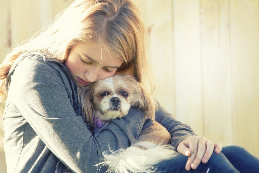 teenager hugging her pet dog