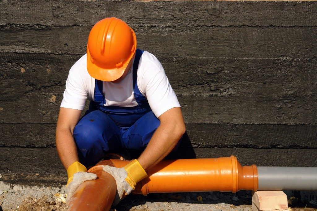 man installing a sewage system
