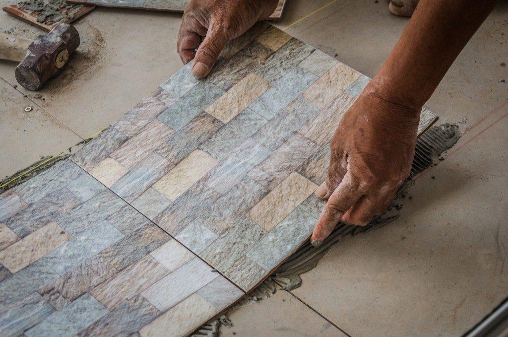 man installing stone flooring