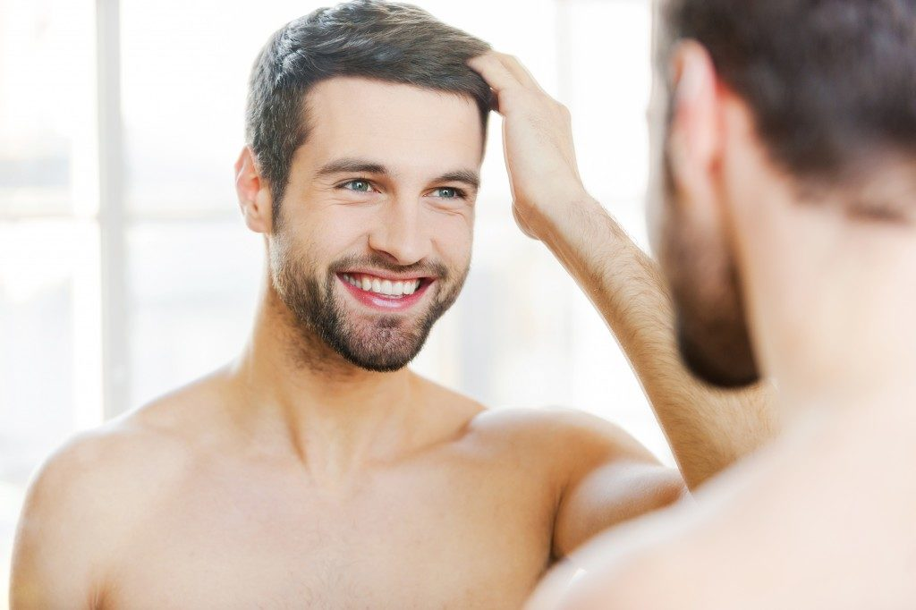 man smiling looking at the mirror