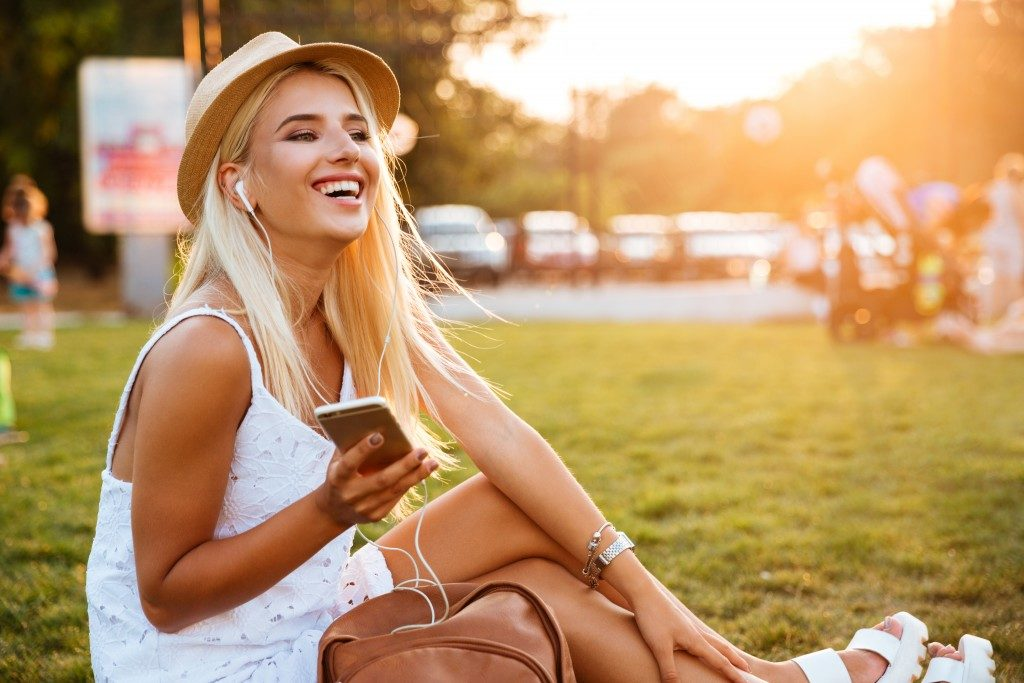 woman happily listening to a playlist on her phone