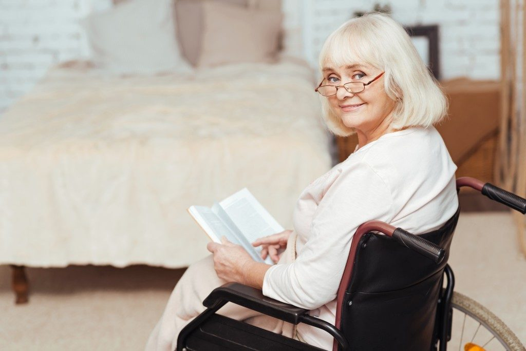 senior in wheelchair holding a book