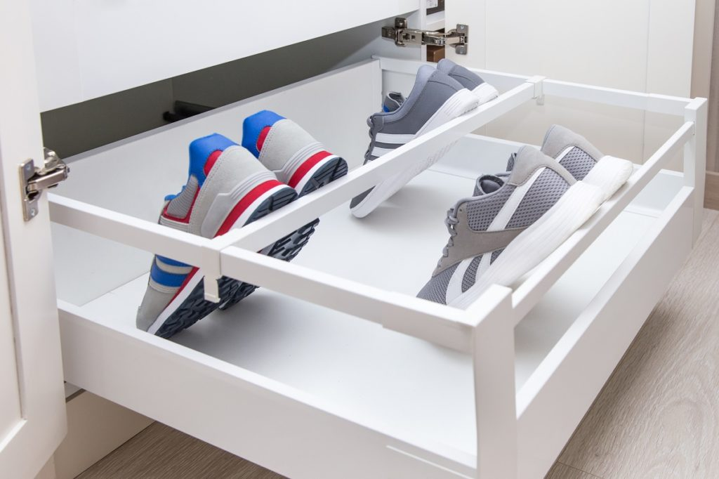 pairs of rubber shoes in a cabinet