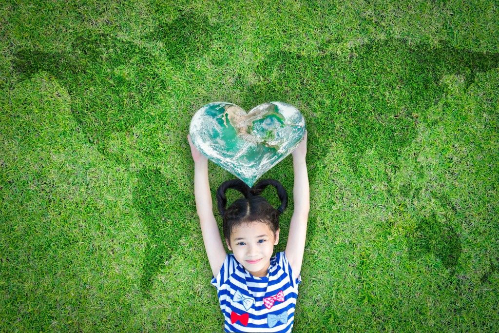 child holding a heart shaped earth